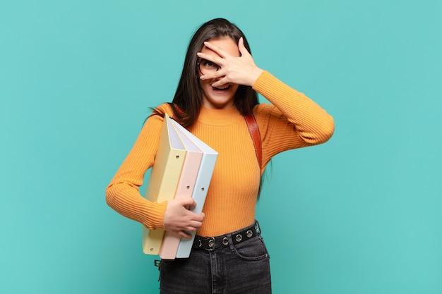 Jonge mooie vrouw die geschokt, bang of doodsbang kijkt, haar gezicht bedekt met de hand en tussen de vingers gluurt. studentenconcept