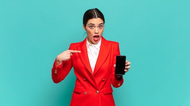 Jonge mooie vrouw die geschokt en verrast kijkt met wijd open mond, wijzend naar zichzelf. slimme telefoon concept