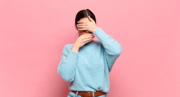 Jonge mooie vrouw die gezicht bedekt met beide handen die nee zeggen! foto's weigeren of foto's verbieden