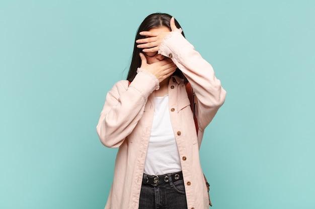 Jonge mooie vrouw die gezicht bedekt met beide handen en nee zegt tegen de camera! foto's weigeren of foto's verbieden. studentenconcept Premium Foto