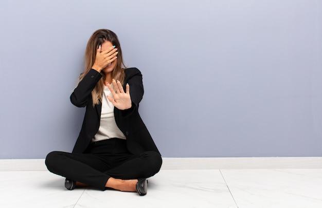 Jonge mooie vrouw die gezicht behandelen met hand en andere hand vooraan zetten om camera tegen te houden, die foto's of beelden bedrijfsconcept weigeren