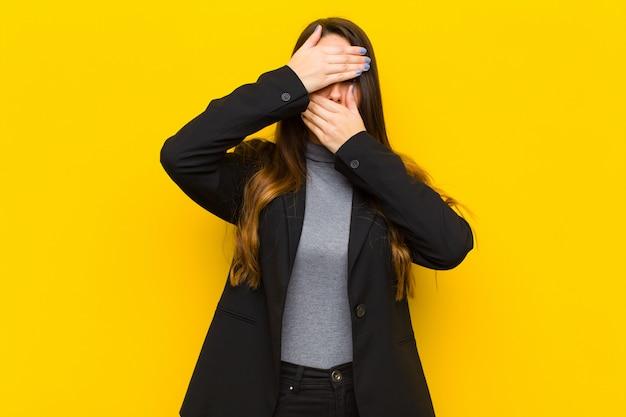 Jonge mooie vrouw die gezicht behandelt met beide handen die nee tegen de camera zegt! afbeeldingen weigeren of foto's verbieden baan of bedrijfsconcept