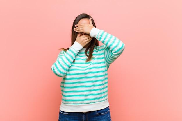 Jonge mooie vrouw die gezicht behandelt met beide handen die nee tegen de camera zegt! afbeeldingen weigeren of foto's verbieden tegen roze muur