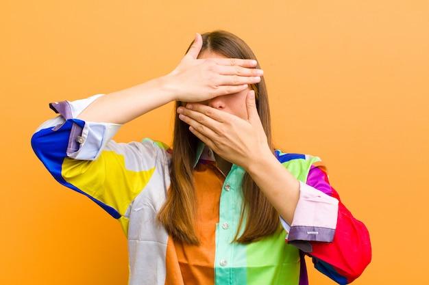 Jonge mooie vrouw die gezicht behandelt met beide handen die nee zeggen tegen de camera! afbeeldingen weigeren of foto's verbieden die tegen een vlakke muur zijn geïsoleerd