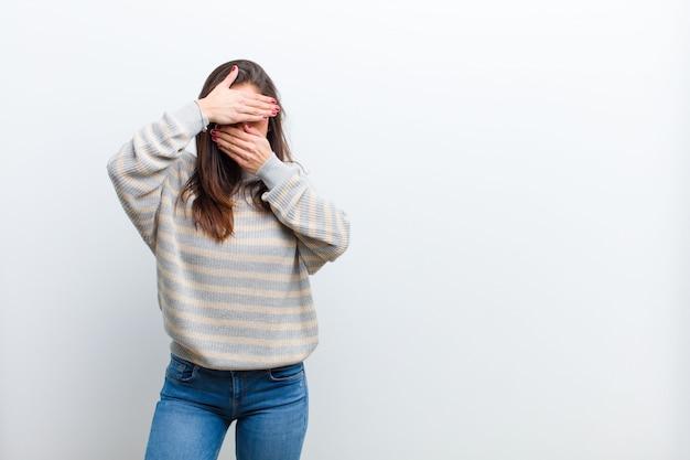 Jonge mooie vrouw die gezicht behandelt met beide handen die nee zeggen tegen de camera! afbeeldingen weigeren of foto's verbieden die tegen een witte muur worden geïsoleerd