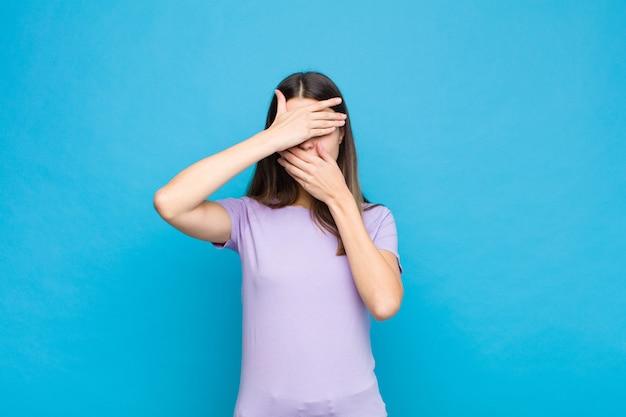 Jonge mooie vrouw die gezicht behandelt met beide handen die nee zeggen tegen de camera! afbeeldingen weigeren of foto's verbieden tegen een blauwe muur
