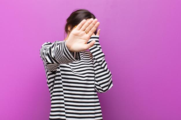 Jonge mooie vrouw die gezicht behandelt met hand en andere hand vooraan zet om camera tegen te houden, die foto's of beelden over purpere muur weigert