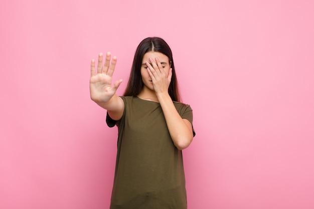 Jonge mooie vrouw die gezicht behandelt met hand en andere hand vooraan zet om camera tegen te houden, die foto's of beelden tegen roze muur weigert