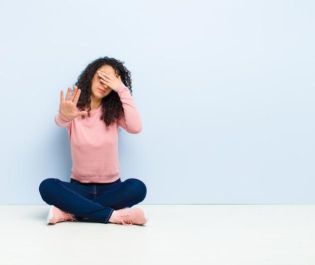 Jonge mooie vrouw die gezicht behandelt met hand en andere hand vooraan zet om camera tegen te houden, die foto's of beelden weigert zittend op vloer