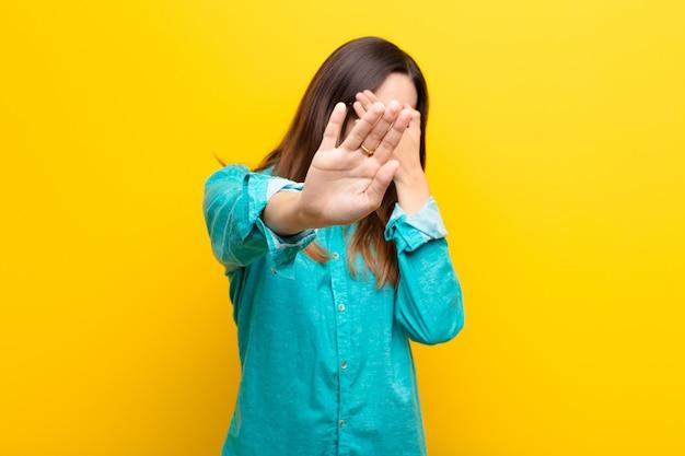Jonge mooie vrouw die gezicht behandelt met hand en andere hand vooraan zet