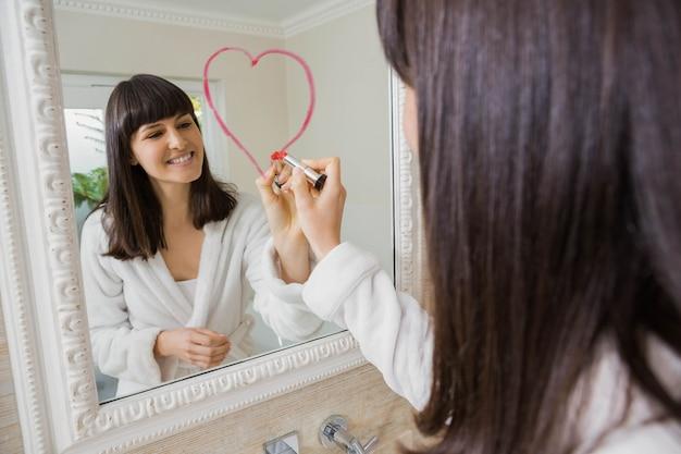 Jonge mooie vrouw die groot hart trekt op spiegel met lippenstift