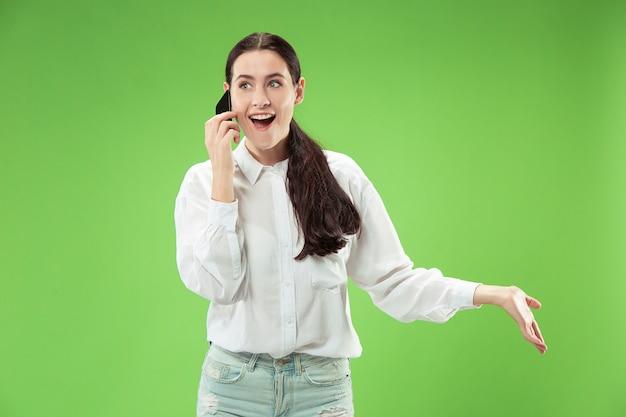 Jonge mooie vrouw die gsm-studio op de groene achtergrond van de kleurenstudio met behulp van. menselijke gezichtsemoties concept. trendy kleuren