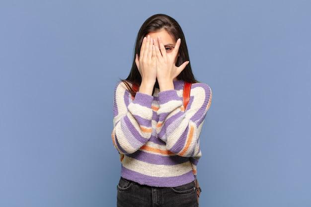 Jonge mooie vrouw die haar gezicht bedekt met handen, tussen de vingers gluurt met een verbaasde uitdrukking en naar de zijkant kijkt. studentenconcept