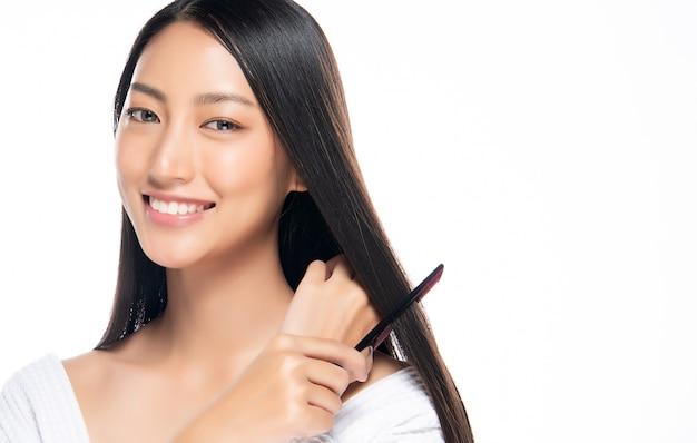 Jonge mooie vrouw die haar haar op witte achtergrond kamt.