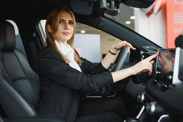 Jonge mooie vrouw die haar liefde toont aan een auto in een autoshowroom