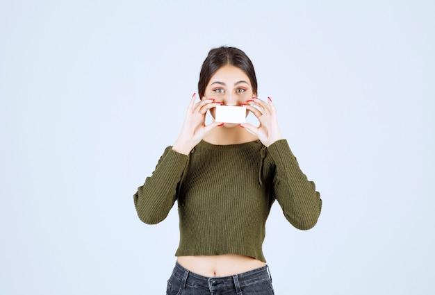 Jonge mooie vrouw die haar mond bedekt met een blanco visitekaartje.