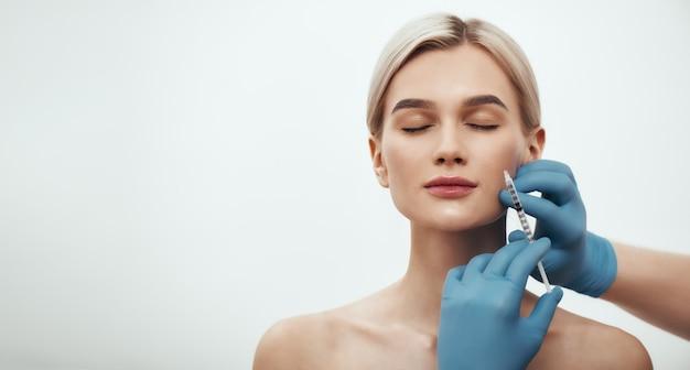 Jonge mooie vrouw die haar ogen gesloten houdt terwijl artsen een injectie in haar maken