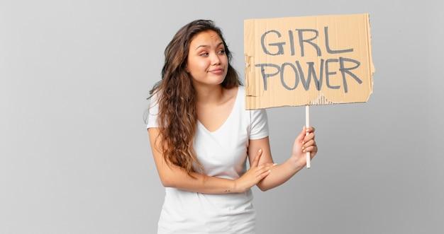 Jonge mooie vrouw die haar schouders ophaalt, zich verward en onzeker voelt en een girlpower-banner vasthoudt