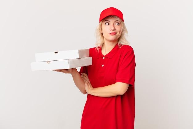 Jonge mooie vrouw die haar schouders ophaalt, zich verward en onzeker voelt. pizza bezorgconcept