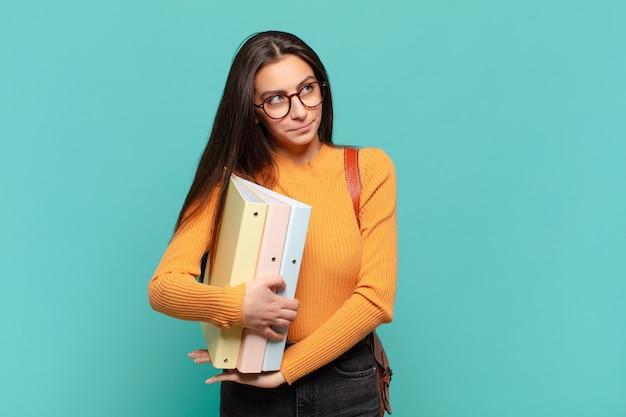 Jonge mooie vrouw die haar schouders ophaalt, zich verward en onzeker voelt, twijfelend met gekruiste armen en een verbaasde blik. studentenconcept