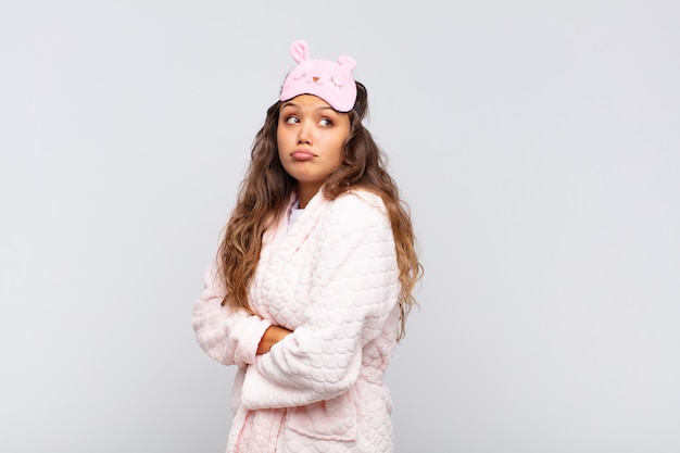 Jonge mooie vrouw die haar schouders ophaalt, zich verward en onzeker voelt, twijfelt met gekruiste armen en een verbaasde blik in een pyjama