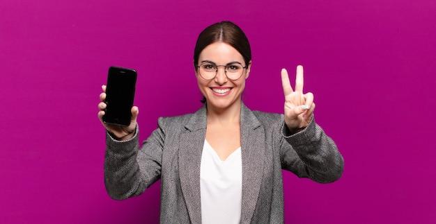 Jonge mooie vrouw die haar telefoon met het lege scherm toont. bedrijfsconcept