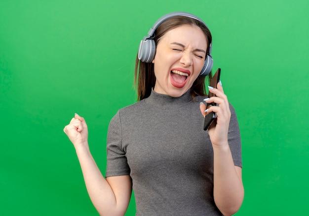 Jonge mooie vrouw die hoofdtelefoons draagt die met gesloten ogen en gebalde vuist zingen en mobiele telefoon als microfoon gebruiken die op groene achtergrond wordt geïsoleerd