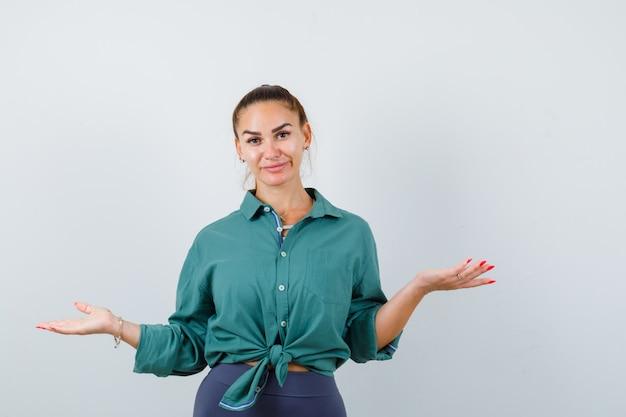 Jonge mooie vrouw die hulpeloos gebaar in groen shirt toont en er verward uitziet. vooraanzicht.