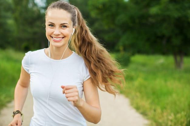 Jonge mooie vrouw die in het park loopt en naar muziek luistert met een koptelefoon.