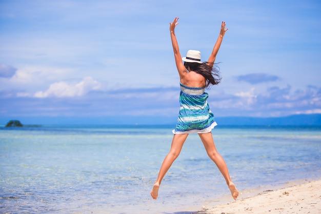 Jonge mooie vrouw die in het strand springt