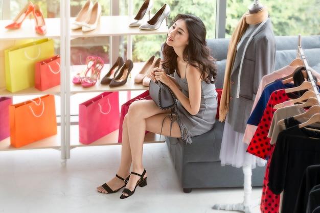 Jonge mooie vrouw die in het winkelen bij winkel genieten van