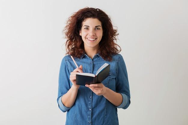 Jonge mooie vrouw die in notitieboekje schrijft met potlood, glimlachen, krullend haar, positief, gelukkig, geïsoleerd, denim blauw shirt, hipsterstijl, student leren, in de camera kijken, aantekeningen maken, onderwijs