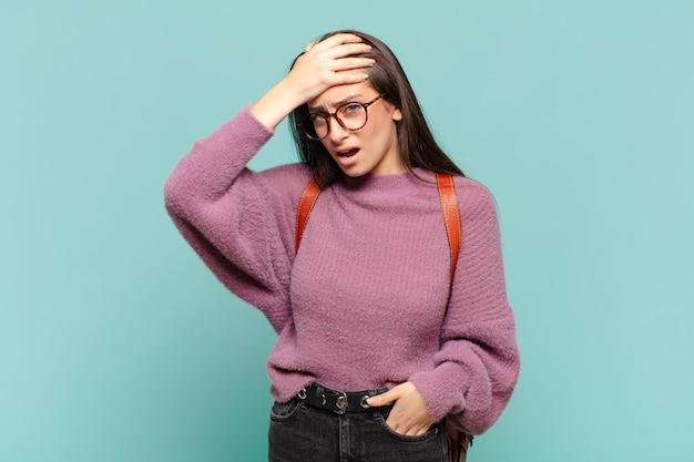 Jonge mooie vrouw die in paniek raakt over een vergeten deadline, zich gestrest voelt, een puinhoop of een fout moet verdoezelen. studentenconcept