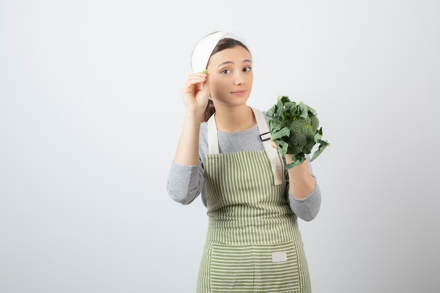Jonge mooie vrouw die in schort verse broccoli op wit houdt