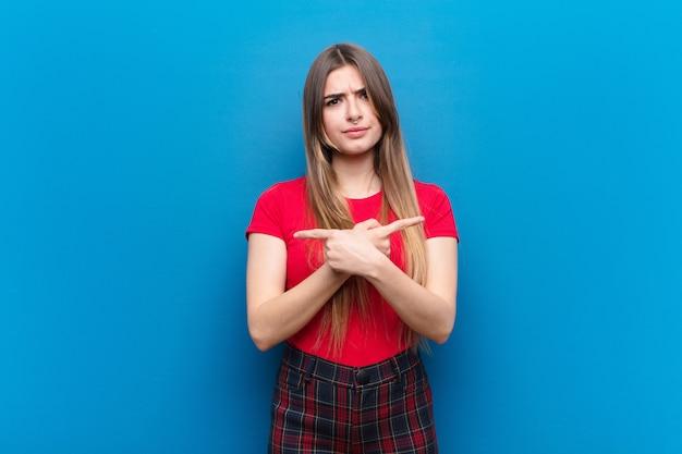 Jonge mooie vrouw die in verwarring gebracht en verward, onzeker en in tegengestelde richtingen met twijfels over blauwe muur kijkt