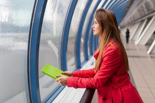 Jonge mooie vrouw die in vrijetijdskleding tabletlaptop in stedelijk gebouw houdt, jeans, roze trenchcoat, bij venster met uitzicht op de stad