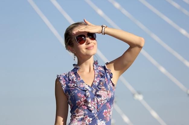 Jonge mooie vrouw die in zonnebril de zon op de blauwe hemel bekijkt