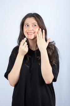 Jonge mooie vrouw die in zwarte uitrusting lippenstift toepast.