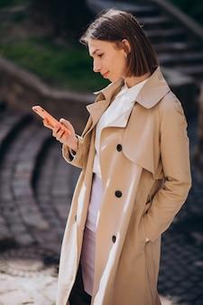 Jonge mooie vrouw die jas draagt die in de stad loopt en aan de telefoon spreekt