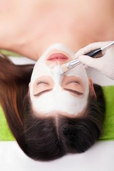 Jonge mooie vrouw die klei gezichtsmasker in de salon van de kuuroordschoonheid ontvangt.