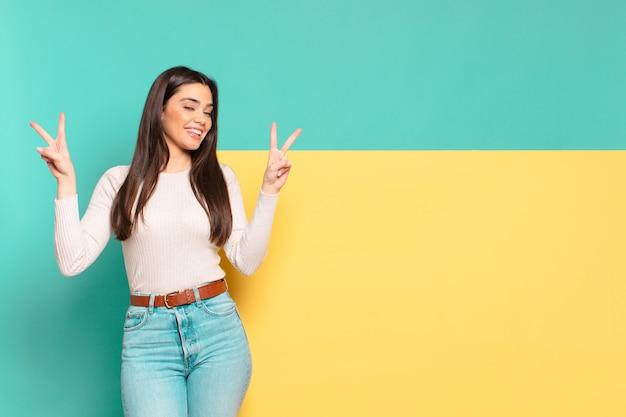 Jonge mooie vrouw die lacht en er gelukkig, vriendelijk en tevreden uitziet, gebarend overwinning of vrede met beide handen. kopieer ruimte om uw concept te plaatsen