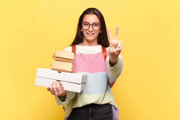 Jonge mooie vrouw die lacht en er gelukkig, zorgeloos en positief uitziet, gebarend overwinning of vrede met één hand. neem een fastfoodconcept
