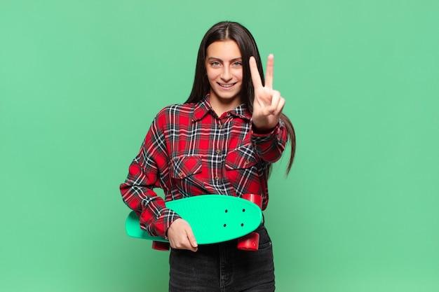 Jonge mooie vrouw die lacht en er gelukkig, zorgeloos en positief uitziet, gebarend overwinning of vrede met één hand. skate board concept
