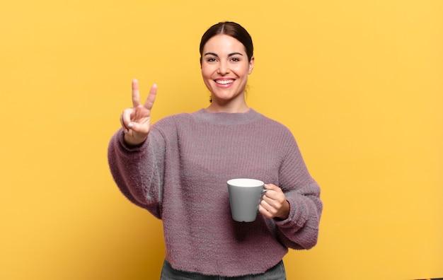Jonge mooie vrouw die lacht en er gelukkig, zorgeloos en positief uitziet, gebarend overwinning of vrede met één hand
