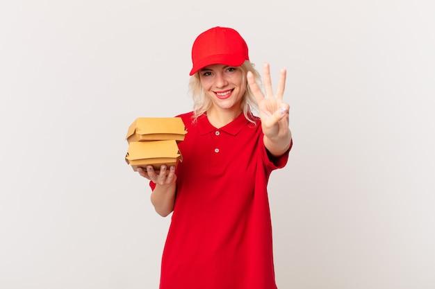 Jonge mooie vrouw die lacht en er vriendelijk uitziet, met nummer drie. hamburger bezorgconcept