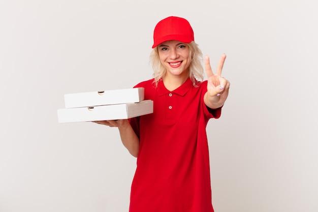 Jonge mooie vrouw die lacht en er vriendelijk uitziet, met nummer twee. pizza bezorgconcept