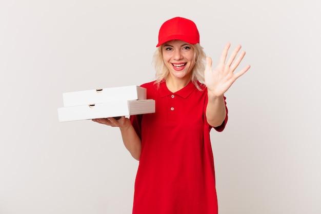 Jonge mooie vrouw die lacht en er vriendelijk uitziet, met nummer vijf. pizza bezorgconcept