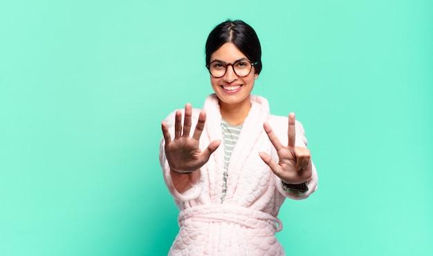 Jonge mooie vrouw die lacht en er vriendelijk uitziet, nummer acht of achtste toont met de hand naar voren, aftellend. pyjama concept