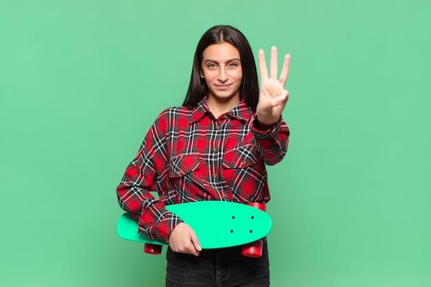 Jonge mooie vrouw die lacht en er vriendelijk uitziet, nummer drie of derde toont met de hand naar voren, aftellend. skate board concept