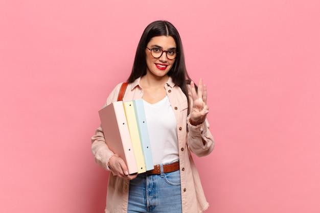 Jonge mooie vrouw die lacht en er vriendelijk uitziet, nummer drie of derde toont met de hand naar voren, aftellend. studentenconcept